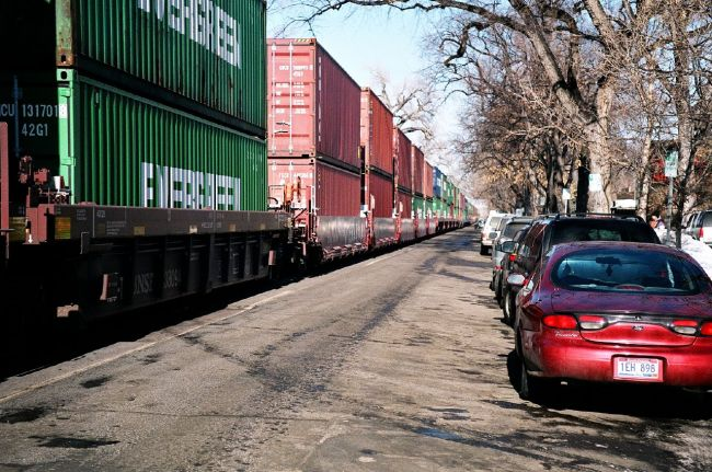 freight containers train along street of parked cars